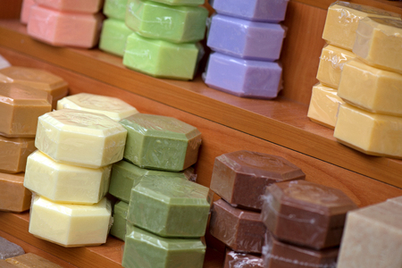 Natural, handmade soaps in shape of honeycomb standing in shelf sorted by colors. Wooden background