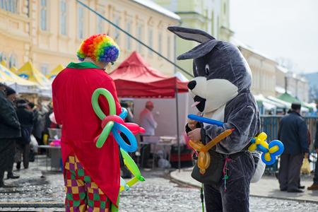 Maskotka wielkanocnego zajączka i niezależny klaun tworzący balonowe zwierzęta i różne kształty na festiwalu plenerowym w centrum miasta.