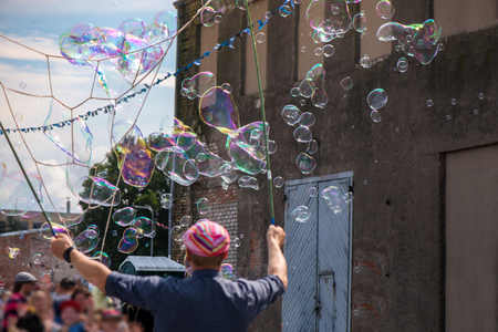 A freelance clown blowing hundreds of tiny, small and big bubbles at outdoor festival in city center. Concept of entertainment, birthdays. Kids having fun. Shower of bubbles flying in the happy crowd Stock Photo