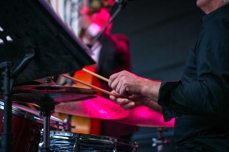 Foto de un hombre tocando la batería en el escenario durante el festival de música en verano. Banda interpretando sus canciones de jazz. Concierto en vivo de música electrónica por la noche. Músicos masculinos tocando saxofón, batería, violonchelo