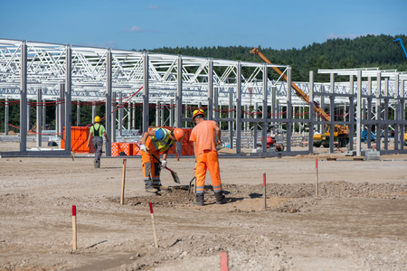 Industrial construction site of new commercial shopping mall. Workers in front, concrete piles foundation for the building, cranes and trucks in background. Ongoing framing, construction of factory. Stock Photo