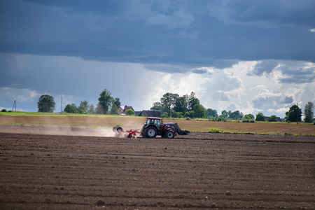 Agricultural background. Tractor pulling plow, throwing dust in air. Combine harvester at wheat field. Heavy machinery during cultivation, working on fields. Dramatic sky, sun rays, rain, storm clouds