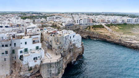 Beautiful view of old town in Polignano a Mare in Italy. Houses and buildings built on cliffs next to ocean or sea. Luxury lifestyle at the edge of the world. Concept of travelling and summer holidays Imagens
