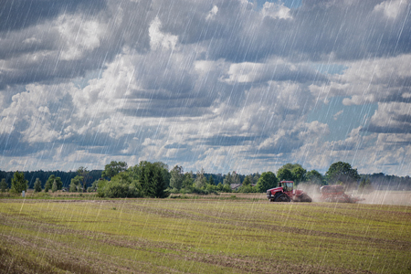 Agricultural background. Red tractor pulling plow, throwing dust in air. Combine harvester at wheat field.
