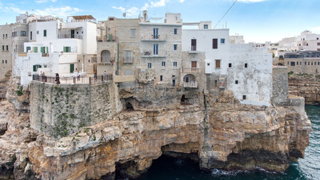 Beautiful view of old town in Polignano a Mare in Italy. Houses and buildings built on cliffs next to ocean or sea.