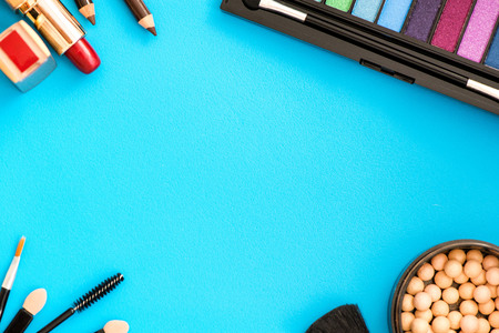 Top, up view of professional cosmetics, makeup background. Brushes, eye shadows, eyebrow pencils, powder, bronzing balls, mascara, red lipstick.