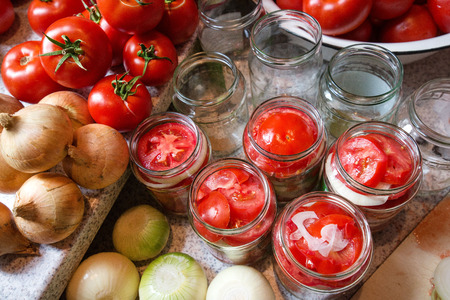 Canning fresh tomatoes with onions in jelly marinade. Woman hands putting red ripe tomato slices and onion rings in jars.