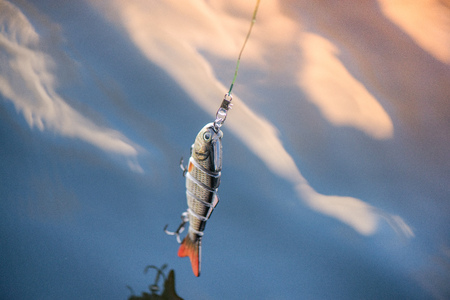 Old plastic spinning bait with reflection on calm water background.