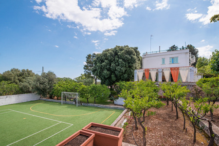 Football field and tennis court next to beautiful villa. Concept of leisure, sport and recreation. Sunny summer day. Time for outdoor activities with family.