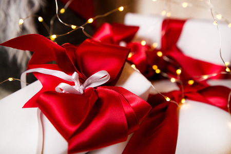 Lovely presents under Christmas tree, gift boxes on white, fluffy, cozy blanket background with glowing reindeer decoration and fairy lights. Concept of holidays, giving gifts, love and surprises.