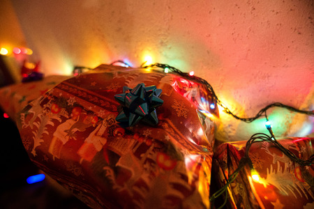 Decorated Christmas gifts standing in shelf next to Christmas lights Stock Photo