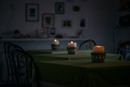 Lit up candle in wicker wooden basket standing on table in restaurant or dining room on green, natural linen tablecloth. Romantic atmosphere for couples, time for dinner. Cosy home, clean sheets
