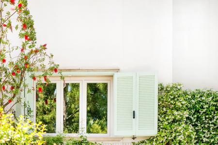 Muur van geopende ramen van een groot huis of appartement. Bloeiende bomen, groene planten en kruiden groeien naast het witte gebouw. Groen wonen. Felle zonnestralen op zonnige zomerdag. Concept van ecologie en natuur
