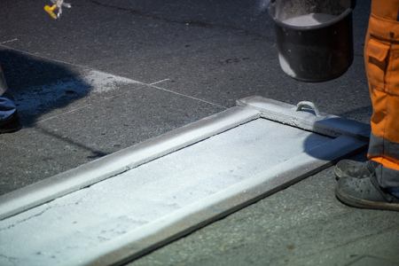 Traffic line painting. Workers are painting white street lines on pedestrian crossing Stock Photo