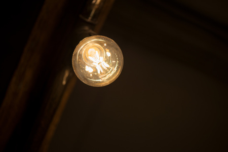 A bright bulb in the middle of the night hung on a ceiling 免版税图像