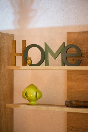 Home is where the heart is. Decorative sign standing in shelf next to old looking vintage books with ornaments. Cozy atmosphere in home or apartment.