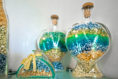 Colorful pebbles or sand in glass bottles, jars standing on shelf in living room or bathroom creating cosy atmosphere. Modern, stylish design elements in house. Concept of summer beach, spa, wellness