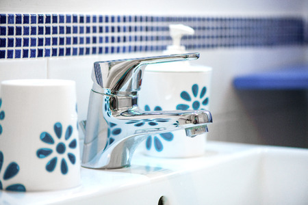 Modern tiled bathroom sink basin faucet paired with clay soap containers.  Concept of cleaning the bathroom. 免版税图像