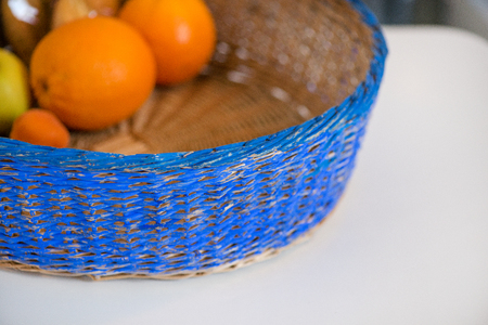 Blue wicker basket full of fruits, apples, oranges, lemons and croissants and bun. Fresh and healthy breakfast. Cozy kitchen. Waiting for dinner.