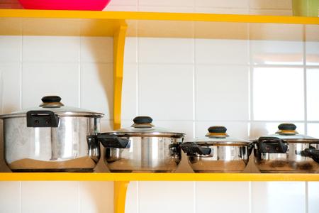 Orange metal soup pots standing on shelf in kitchen. Time to prepare dinner.