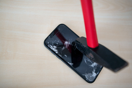 Hammer cracking on smartphone. Screen and display is destroyed, damaged and cracked. Concept of anger, rage and repairing electronic devices. Valid warranty