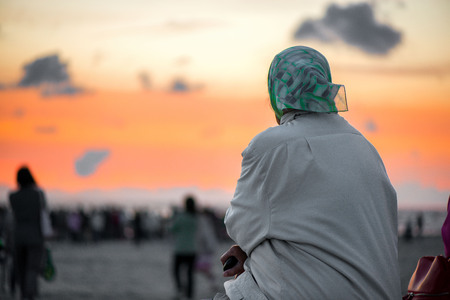 Old woman sitting at the seaside and watching romantic sunset 版權商用圖片