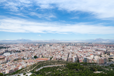 Panoramic view of city from Santa Barbara Castle in Alicante, Spain. Block apartment buildings, parks, roads, houses, palm trees. Beautiful mountain landscape in background, blue sky