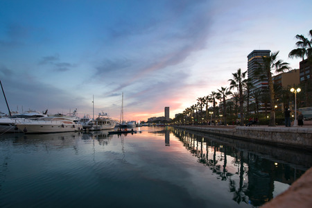 Beautiful port of Alicante, Spain at Mediterranean sea. Luxury yachts, ships, ferries and fishing boats sailing and standing in rows in harbor. Rich people traveling around the world. Sunset evening 版權商用圖片