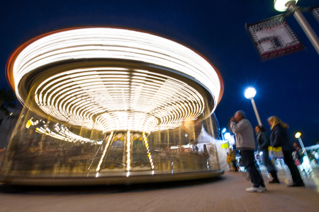 Abstract, long exposure shot of spinning Children's vintage Carousel at an amusement park in the evening and night illumination. Beautiful, bright carousel in Alicante, Spain