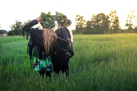 Beautiful girls with blonde hair, leather jackets and flower crowns walking in meadow during sunset. Romantic, relaxing nature. Concept of recreation, meditation and spiritual healing and friendship