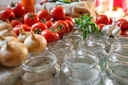 Canning fresh tomatoes with onions in jelly marinade. Woman hands putting red ripe tomato slices and onion rings in jars. Basil, parsley leaves on top of onions. Vegetable salads for winter Фото со стока