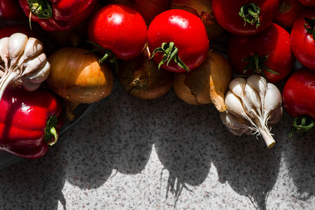 Ripe fresh harvested vegetables on table. Onions, tomatoes, garlic, pepper. Making delicious vegetarian meal or canning veggies for winter in jars. Concept of healthy eating