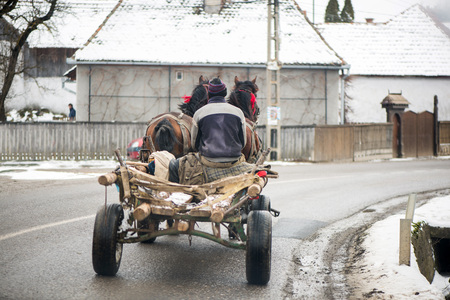 Traditional transylvanian horses are walking through Romanian village,  Concept of hard working animals. Man sitting in wooden cart pulled by two horses. Peasants on a horse-drawn carriage 免版税图像 - 118854528