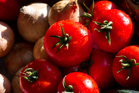 Ripe, fresh, harvested vegetables on table. Onions, tomatoes, garlic on kitchen table prepared to make a delicious vegetarian meal or for canning veggies for winter in jars. Concept of healthy eating