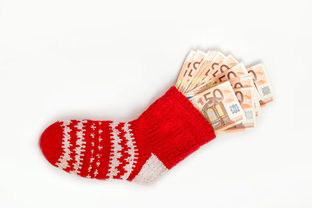 Traditional red Christmas sock stuffed with money on white background.  Concept of gifts, saving and hiding money in safe place.