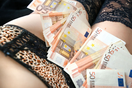 Woman in lingerie with large number of euro money laying on bed. Half body. Concept of dirty money
