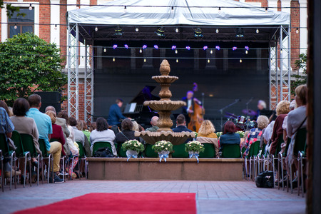 Fountain, red carpet in crowded event. Audience enjoying romantic and relaxing evening and enjoying the culture. Concert venue with jazz musicians playing songs on stage. Beautiful wedding celebration