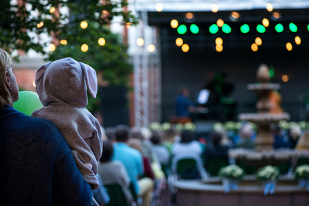 Mom is holding her son or daughter in hoodie with bunny ears and enjoying the culture. Romantic evening in concert venue with jazz musicians playing songs on stage. Beautiful wedding celebration Imagens