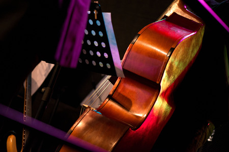 Wooden cello or violin on stage prepared for playing. Music sheets and notes on stand. Classical instruments. Concept of orchestra music. Audience waiting for concert to begin
