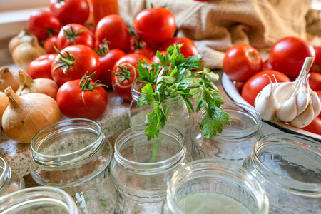 Canning fresh tomatoes with onions in jelly marinade. Woman hands putting red ripe tomato slices and onion rings in jars. Basil, parsley leaves on top of onions. Vegetable salads for winter 写真素材