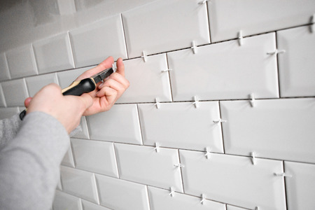 Ceramic tile lying. Installing new subway or metro tile in bathroom, shower or kitchen back splash during home renovation. Placing or taking out tile spacers with hands and pliers.