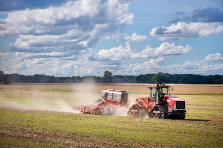 Agricultural background with red tractor pulling plow, throwing dust in air. Combine harvester at wheat field. Heavy machinery during cultivation, working on fields. Dramatic sky, rain, storm clouds Standard-Bild - 118857535