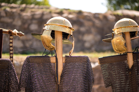 Medieval knight's iron chain armor and golden helmets on wooden cross hanger in a row. Reenactment festival in summer. Preparing for fight and battle. Weapons, shields, armor ready Stock Photo