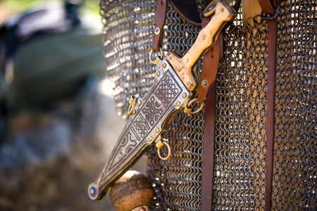 Silver or bronze medieval dagger with ornaments attached to chain armors, hanging in leather strip. Soldiers ready for battle. Reenactment festival in summer. Stockfoto
