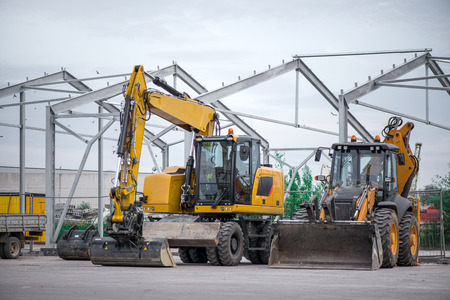 Multiple cars, excavators, trucks, loaders, concrete mixers and construction machinery in large parking lot in industrial territory, next to concrete and asphalt factory Stock Photo