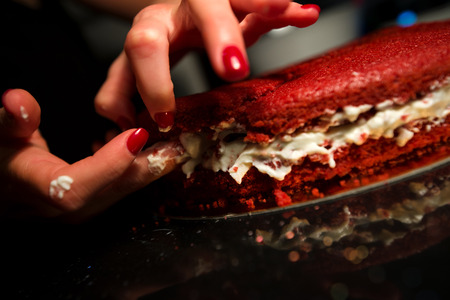 Woman spreading whipped cream with fingers inside freshly made cake. Beautiful home made red velvet cake decorated with whipped cream and raspberry crumbs. Concept of anti sanitary cooking