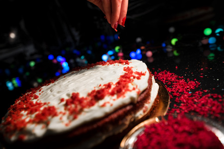 Woman sprinkling raspberry crumbs, icing sugar over freshly made cake, creating ornaments and decorating dessert. Beautiful home made red velvet cake decorated with whipped cream and raspberry crumbs Stock Photo