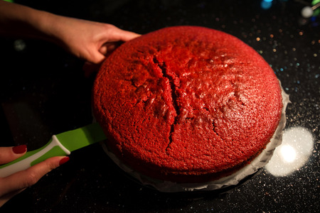 Cutting biscuits. Woman is cooking in kitchen, baking a red velvet cake. Taking out or putting a biscuit tray filled with dough in oven. Delicious, homemade dessert Фото со стока