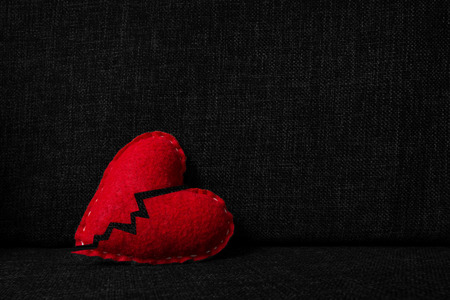 Broken red valentines day heart made from wool on dark fabric background. Split in two parts. Concept of heartbrake, end of relationship and divorce. Standard-Bild