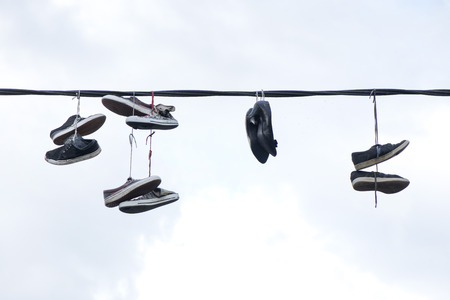 Old sneakers and high heel shoes hanging on electrical wire on overcast background.